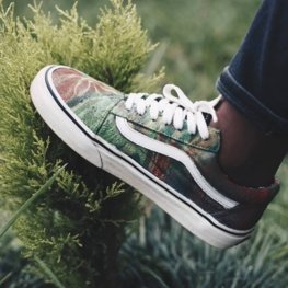 Green hand painted shoe on a natural background with bush and grass