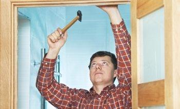 Carpenter hammering in a door frame