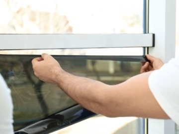 Professional worker tinting window with foil indoors, closeup