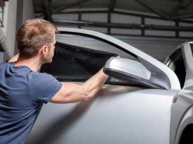 Window tinter in a short sleeve blue shirt applying a tinting film to the window of a silver car