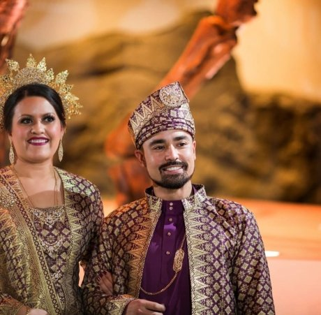 Coach Ryan wedding at the Houston Museum of Natural Science wearing traditional Malay attire.