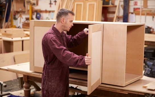 Carpenter in burgundy overalls putting the final touches on a custom made cabinet