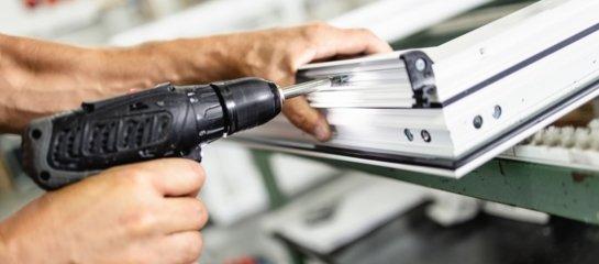 Southern Highlands aluminium worker screwing an aluminium frame to a window