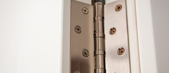 Close up of an aluminium door hinge that is open to reveal the screws