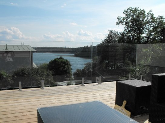 Deck in Sydney's North shore with frameless glass balustrades overlooking a valley of water
