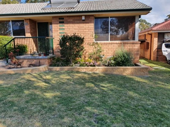 Front shot of stone retaining wall with a brick house in the background. Photo taken in the Southern Highlands, NSW
