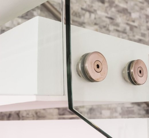 Closeup of a glass balustrade fixture in place on a staircase in a Sydney home